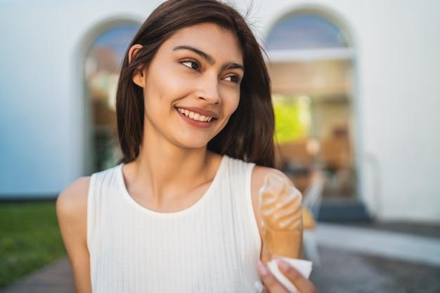 Retrato de jovem aproveitando o tempo ensolarado enquanto toma um sorvete ao ar livre