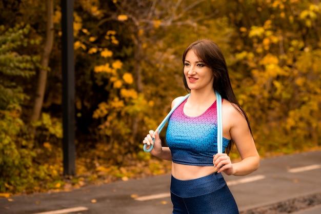 Retrato de jovem apto com corda de pular no parque outono. fêmea de aptidão segurando a corda de pular antes de seu treino ao ar livre. ela usa roupas esportivas brilhantes. garota esportiva está sorrindo