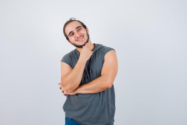 Retrato de jovem apto masculino em pose pensativa com capuz sem mangas e vista frontal alegre
