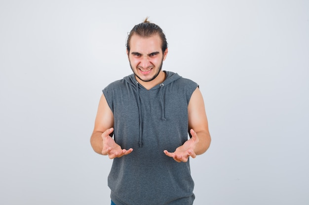Retrato de jovem apto masculino, mantendo as mãos de maneira agressiva em um moletom sem mangas e olhando de frente com raiva