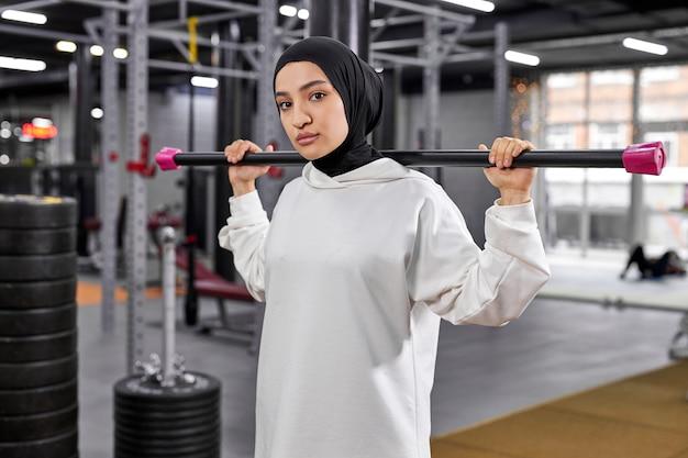 Retrato de jovem árabe se exercitando com pesos na academia, ela fica olhando para a câmera, séria e confiante, usando um hijab esportivo branco