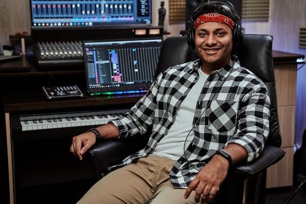 Retrato de jovem artista feliz sorrindo para a câmera enquanto está sentado no estúdio de gravação