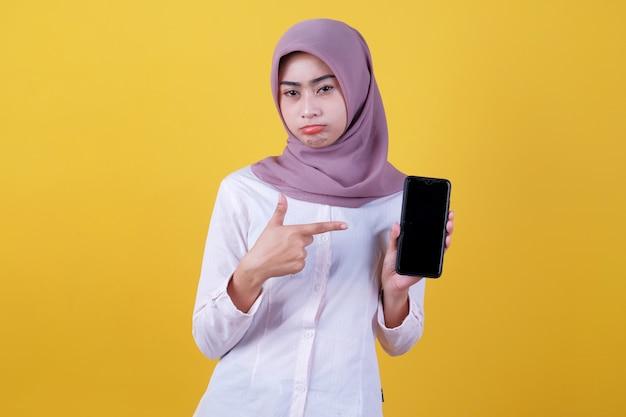 Retrato de jovem asiática com gesto carrancudo, usando um hijab apontando para o smartphone, mostrando a tela do dispositivo