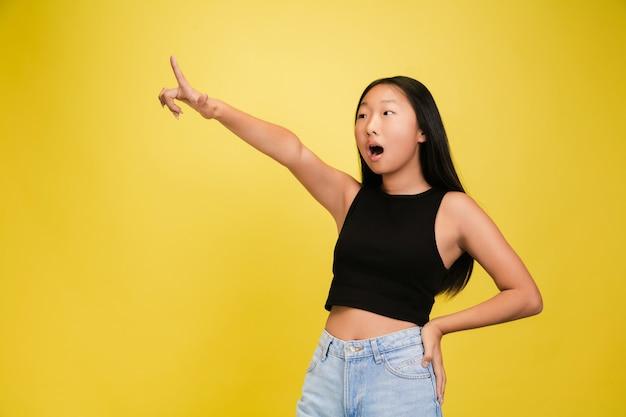 Retrato de jovem asiática isolada na parede amarela
