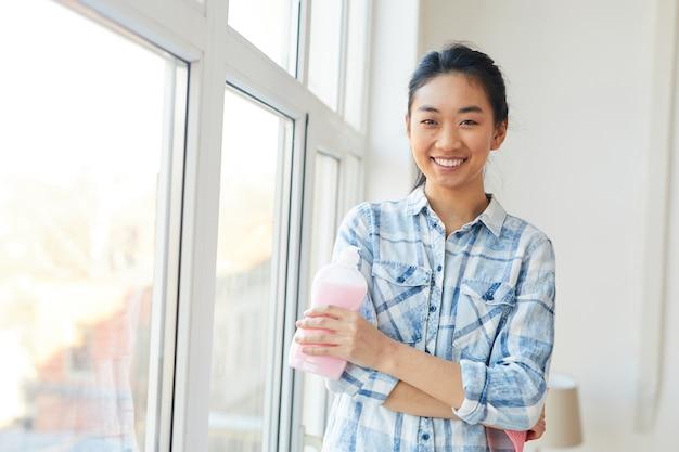 Retrato de jovem asiática sorrindo enquanto lava as janelas e aproveita a limpeza de primavera
