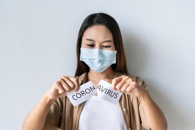 Retrato de jovem asiática usando máscara médica rasga o papel com a palavra coronavirus