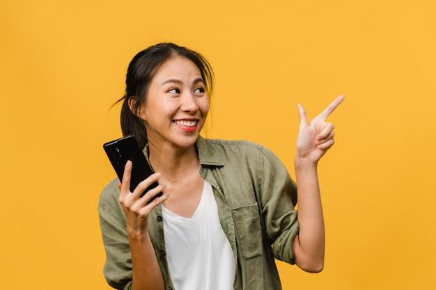 Retrato de jovem asiática usando telefone celular com expressão alegre, mostra algo incrível no espaço em branco em roupas casuais e fica isolado sobre a parede amarela. conceito de expressão facial.