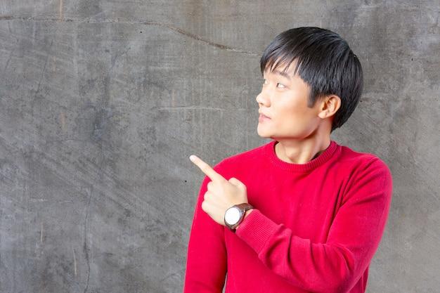 Retrato de jovem asiático, apontando com o dedo