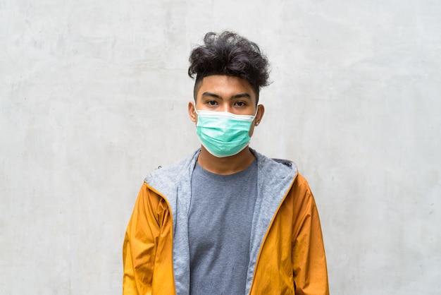 Retrato de jovem asiático com cabelo encaracolado usando máscara para proteção contra surto de coronavírus na parede de concreto