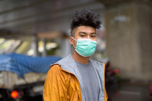 Retrato de jovem asiático com cabelos cacheados usando máscara para proteção contra surto de coronavírus na cidade