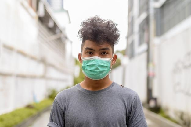 Retrato de jovem asiático com cabelos cacheados usando máscara para proteção contra surto de coronavírus na rua