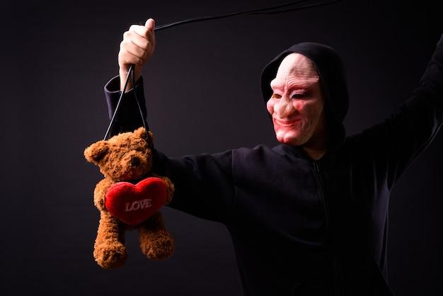 Retrato de jovem asiático com capuz e máscara de terror em preto