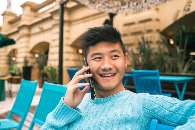 Retrato de jovem asiático falando ao telefone enquanto está sentado em uma cafeteria.