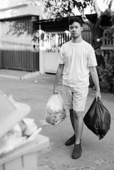 Retrato de jovem asiático levando o lixo para fora de casa