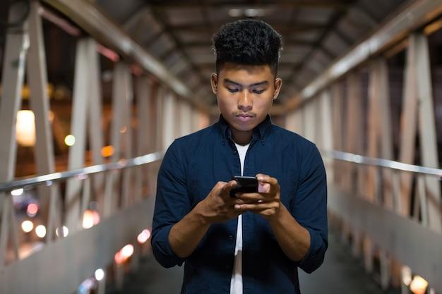 Retrato de jovem asiático na passarela da cidade à noite