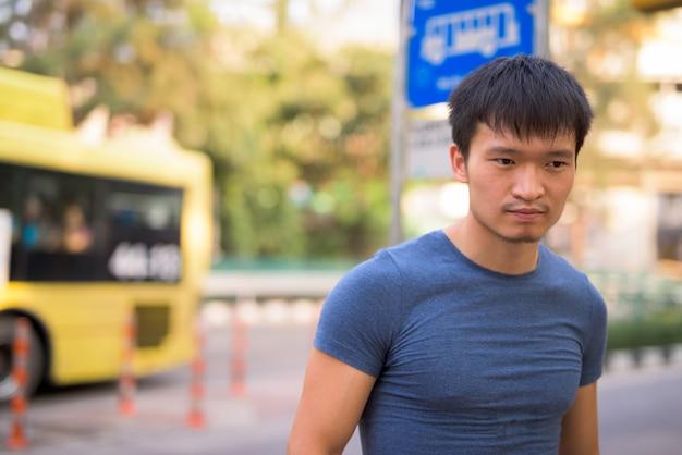 Retrato de jovem asiático no ponto de ônibus