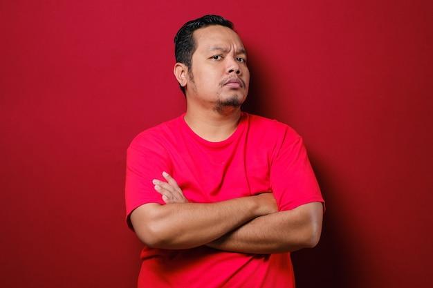 Retrato de jovem asiático olhando para a câmera com uma expressão cínica suspeita, braços cruzados no peito sobre fundo vermelho
