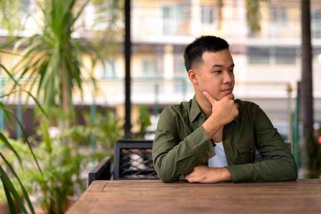 Retrato de jovem asiático relaxando em uma cafeteria