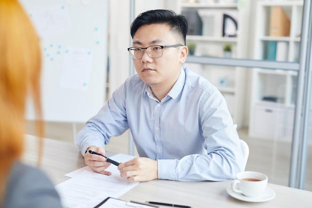 Retrato de jovem asiático respondendo a perguntas durante a entrevista de emprego, sentado em frente ao gerente de rh, copie o espaço