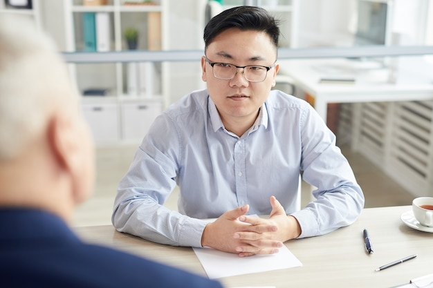 Retrato de jovem asiático respondendo a perguntas durante a entrevista de emprego, sentado em frente ao gerente sênior, copie o espaço