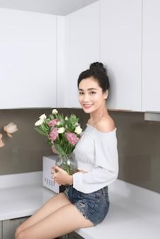 Retrato de jovem asiático segurando o vaso de flores na cozinha.