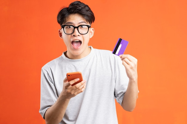 Retrato de jovem asiático segurando um telefone inteligente e um cartão eletrônico, isolado em um fundo laranja