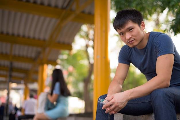 Retrato de jovem asiático sentado no ponto de ônibus