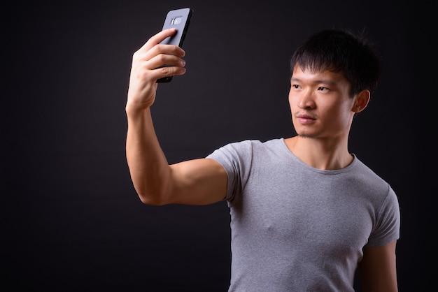 Retrato de jovem asiático tirando selfie com o telefone