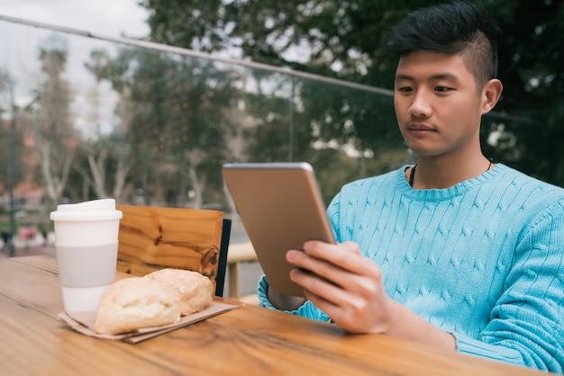 Retrato de jovem asiático usando seu tablet digital enquanto está sentado em uma cafeteria. conceito de tecnologia.