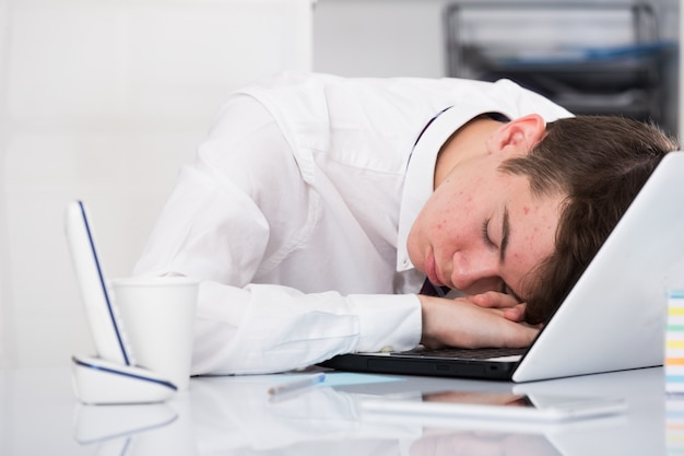 Retrato de jovem assistente dormindo no escritório