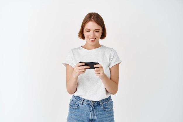 Retrato de jovem assistindo a um vídeo no smartphone, segurando o telefone horizontalmente para jogar videogame, parede branca