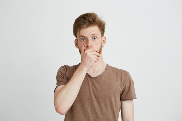 Retrato de jovem assustado assustado surpreso, fechando a boca com as mãos.