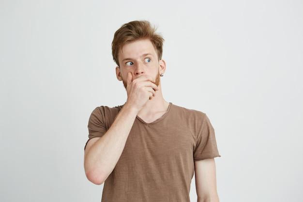 Retrato de jovem assustado assustado surpreso, olhando de lado, fechando a boca com as mãos.