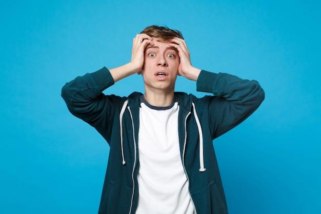 Retrato de jovem assustado chocado em roupas casuais, colocando a mão na cabeça isolada na parede azul. conceito de estilo de vida de emoções sinceras de pessoas.