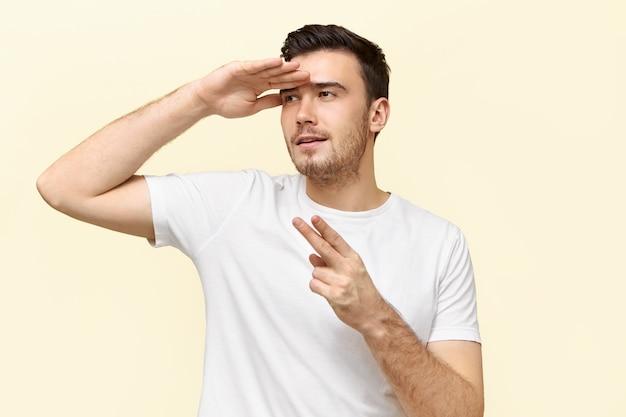 Retrato de jovem ativo e enérgico se divertindo fazendo gestos como se estivesse segurando uma pistola
