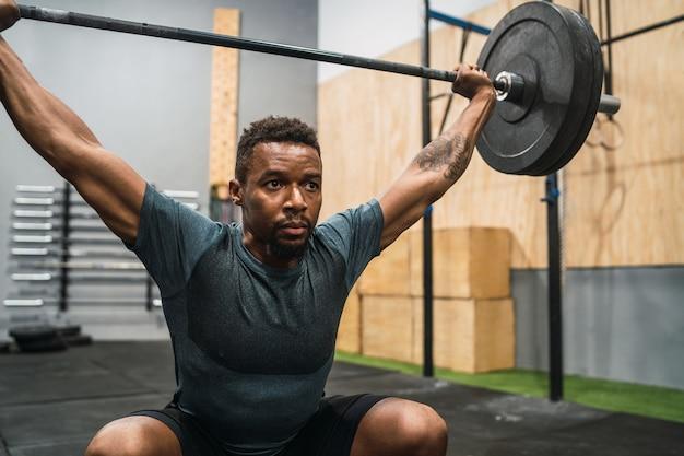 Retrato de jovem atleta crossfit fazendo exercícios com uma barra
