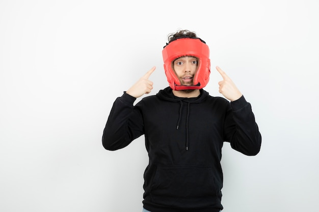 Retrato de jovem atlético em pé de chapéu de boxe vermelho.