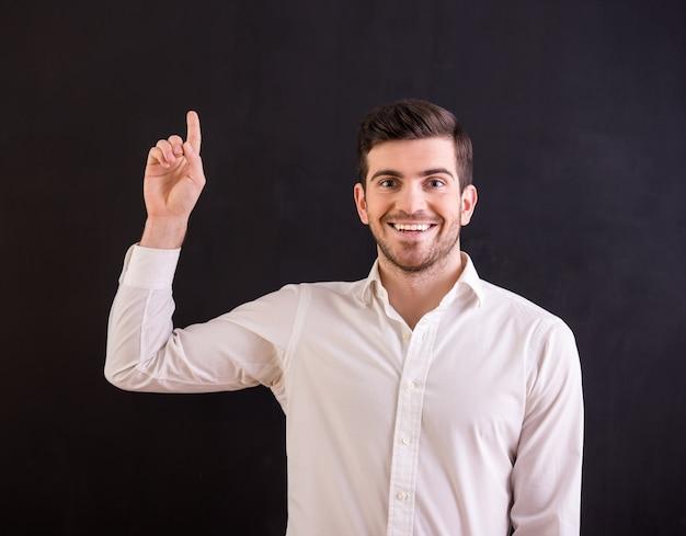 Retrato de jovem atraente aponta o dedo para cima.