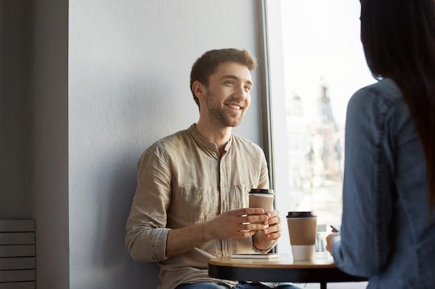 Retrato de jovem atraente barba por fazer, com cabelos escuros, sorrindo, tomando café e ouvindo histórias de namorada sobre um dia difícil no trabalho. estilo de vida, conceito de relacionamento