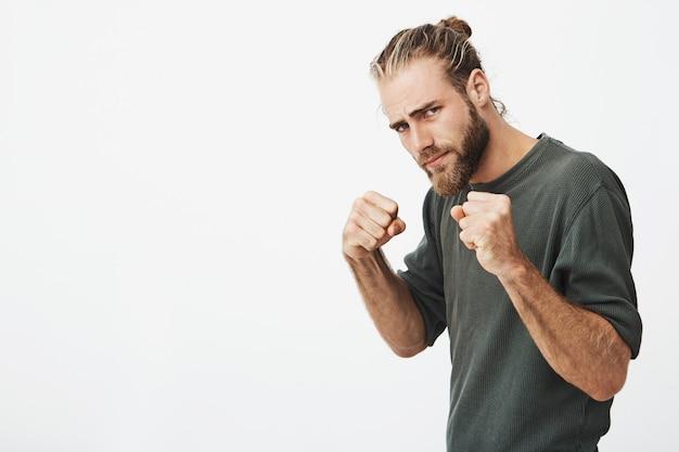 Retrato de jovem atraente com penteado na moda e barba de mãos dadas na frente dele em posição de boxe vai lutar.