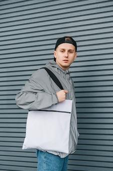 Retrato de jovem atraente em streetwear elegante com saco branco eco no ombro posando em cinza com cara séria.