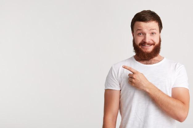 Retrato de jovem atraente feliz moderno com barba usa camiseta parece confiante e aponta para o lado para copyspace com o dedo isolado sobre a parede branca