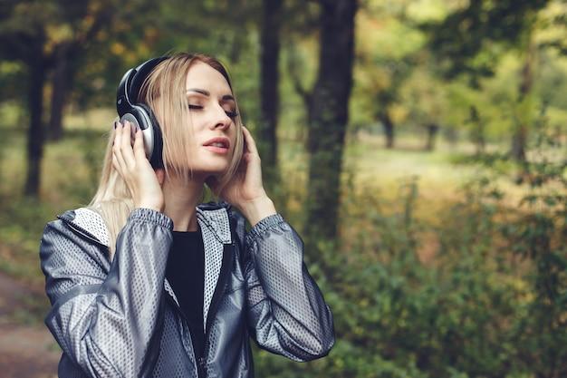 Retrato, de, jovem, atraente, loiro, mulher, ligado, um, parque cidade, escutar música, ligado, fones
