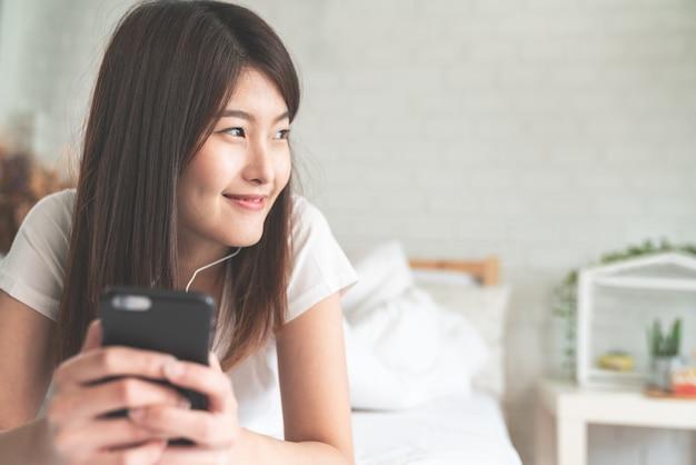 Retrato, de, jovem, atraente, mulher asian, escutar música, em, smartphone