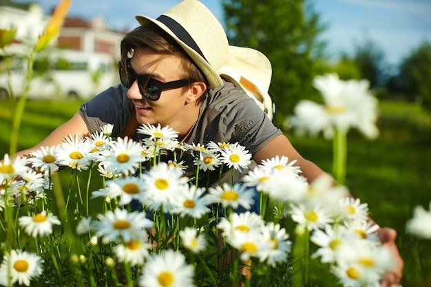 Retrato de jovem atraente sorridente moderno homem elegante em pano casual de chapéu em copos no parque com flores coloridas brilhantes para fotos camomiles