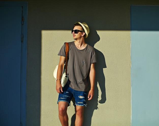 Retrato de jovem atraente sorridente moderno homem elegante em pano casual no chapéu em óculos de sol em pé perto da parede