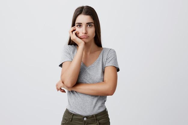 Retrato de jovem atraente triste encantadora aluna caucasiana com cabelos longos escuros na elegante roupa cinza, segurando a cabeça com a mão com expressão infeliz depois de receber a marca ruim