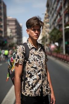 Retrato de jovem autêntico com skate no meio da rua.
