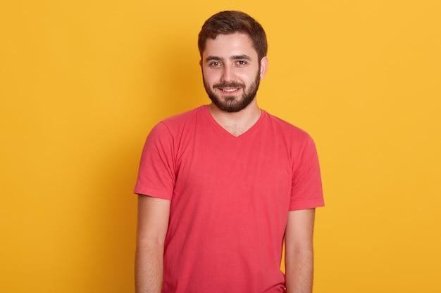 Retrato de jovem barbudo atraente feliz, bonito macho vestindo camiseta casual vermelha, sorrindo