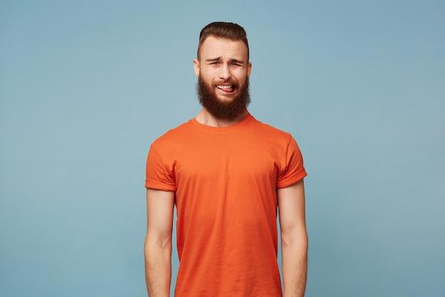 Retrato de jovem barbudo bonito com corte de cabelo estiloso usa camiseta vermelha com aversão a nojo e mostra a língua, isolada no azul